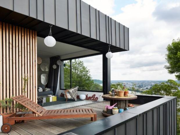 Une maison en zinc noir posée sur un mur en brique