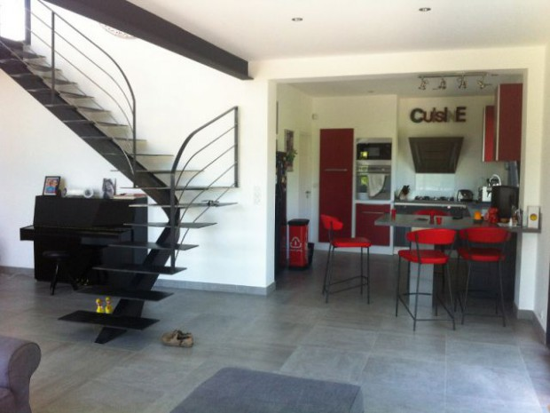 Une cuisine ouverte rouge et un séjour spacieux