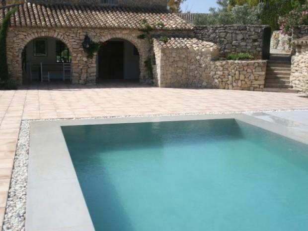 La piscine est partiellement cerclée de galets