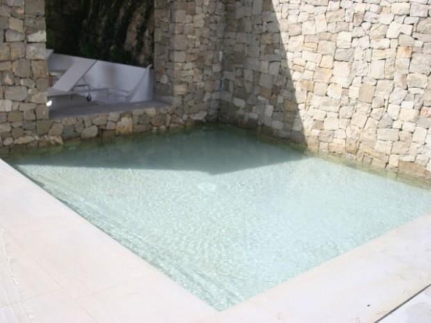 Le mur de pierre plonge dans le petit bassin